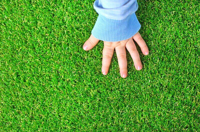 Childs hand resting on artificial grass